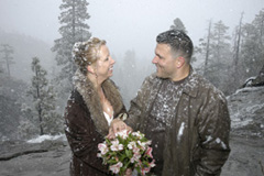 Married couple smile under the falling snow after their wedding