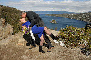 Groom kisses his bride on the overlook of the bay